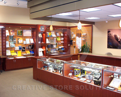 Retail store wall cabinet system with a slatwall back panel to display products.